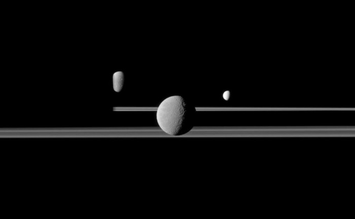 The bright ice moon Enceladus on the right, with Rhea in the foreground, Saturn's second largest moon, and Dione in the back; Saturn is on the left. The giant gas planet has 62 known moons, but only 13 have a diameter of more than 50 Km (Enceladus: about 500 km). Photo: Cassini Imaging Team, SSI, JPL, ESA, NASA