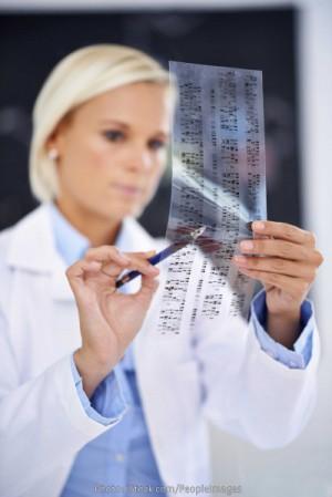 Forscherin mit einer Genkarte aus den typischen DNA-Bandenmustern, die mit Hilfe von Gelelektrophorese erstellt werden. Solche Muster werden für Vaterschaftstests verwendet, für genetische Fingerabdrücke in der Forensik, und für Studien an seltenen Erbkrankheiten wie den FHD. Foto: PeopleImages