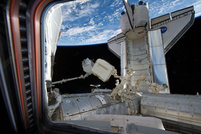The Space Shuttle Endeavour is docked to the ISS during mission STS-134. The  The station's Canadarm2 lifts the Alpha Magnetic Spectrometer-2 from the Shuttle's payload bay for installation on starboard truss on May 19, 2011. Photo: NASA, public domain
