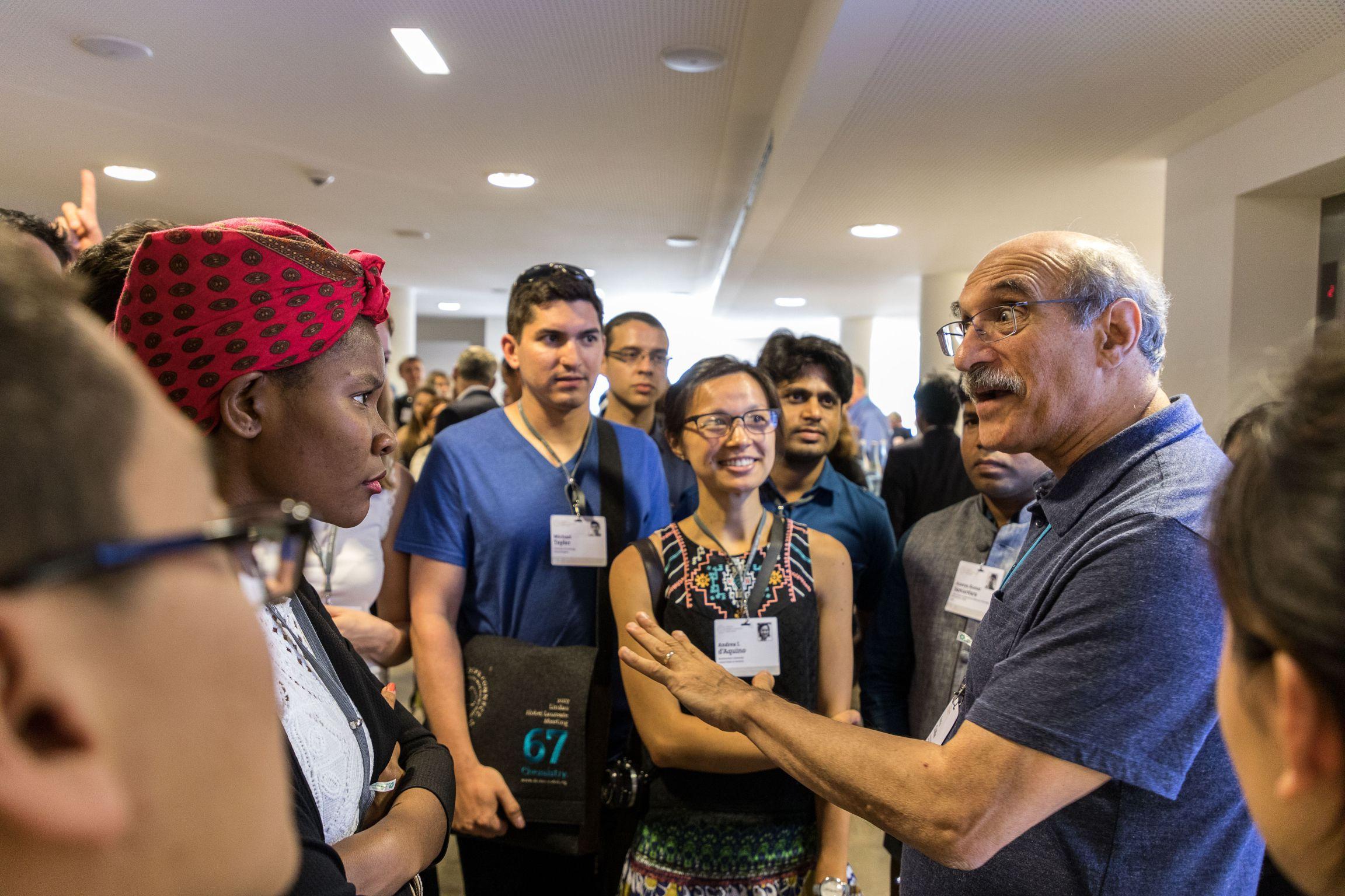 Nachwuchswissenschaftler unterhalten sich mit Nobelpreisträger Martin Chalfie während der 67. Lindauer Tagung, Picture/Credit: Christian Flemming/Lindau Nobel Laureate Meetings