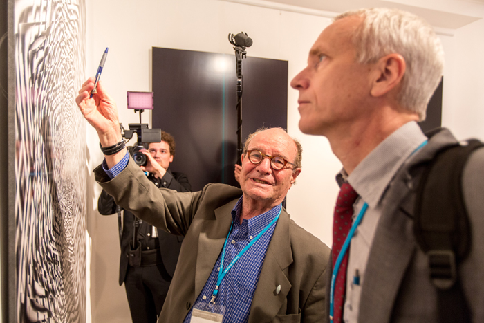 Gilbert guiding fellow Nobel Laureate Brian Kobilka through the Lindau exhibition of his own art in 2013. Photo: C.Flemming/Lindau Nobel Laureate Meetings
