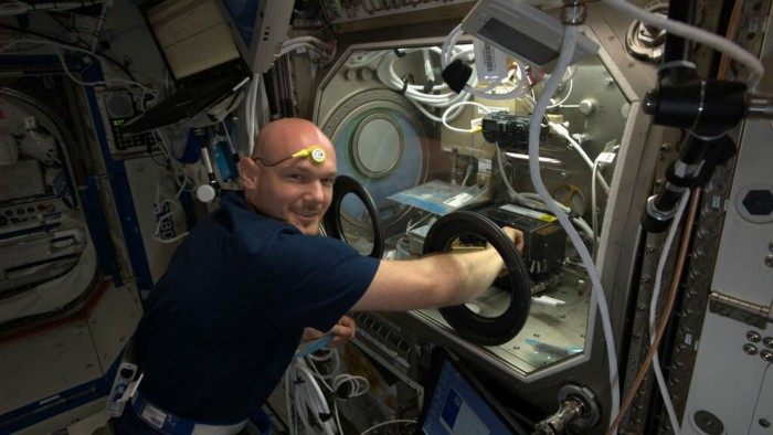 Gerst conducting an experiment, with a temperature sensor on his forehead. Photo: ESA/NASA