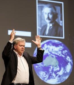 Physiknobelpreisträger Brian Schmidt mit einem Bild seines berühmtesten Vorgängers während seines Vortrags 2014 zum Thema Kosmologie. Seinen aktuellsten Vortrag aus dem Jahr 2015 finden Sie hier. Foto: Rolf Schultes/LNLM