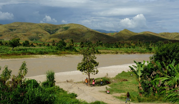 The beautiful landscape of the Artibonite River in Haiti, where the 2010 cholera outbreka started: locals collect their drinking water from the river, and overflowing latrines empty into the river and its tributaries. Photo:  Kendra Helmer, USAID, public domain