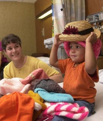 ein fast zweijähriges Mädchen sucht sich einen Hut aus, weil sie ihre Haare durch eine Chemotherapie verloren hat. Sie litt an einem Nierentumor, der nur bei Kindern vorkommt und sehr gut behandelbar ist. Das Bild entstand im Militärkrankenhaus von San Antonio, Texas. Foto: U.S. Air Force photo/Master Sgt. Lance Cheung, Public Domain