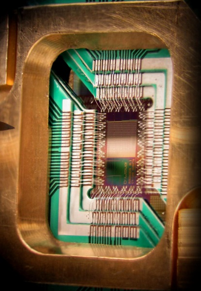 Photograph of a chip constructed by D-Wave Systems Inc., mounted and wire-bonded in a sample holder. The D-Wave processor is designed to use 128 superconducting logic elements that exhibit controllable and tunable coupling to perform operations. Photo: D-Wave Systems Inc., License: Creative Commons Attribution 3.0 Unported license.