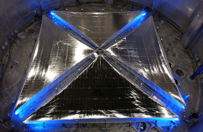 This is how the future of space travel could look like: A 20-meter solar sail system, developed by ATK Space Systems, during testing at NASA Glenn Research Center's Plum Brook facility in Sandusky, Ohio. The sail material is supported by a series of coilable booms, which are extended via remote control from a central stowage container about the size of a suitcase. The sails are made of an aluminized, plastic-membrane material. Photo:  NASA/Marshall Space Flight Center, 2005, public domain